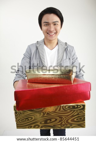 Young man carrying stack of gifts, smiling, portrait - stock photo