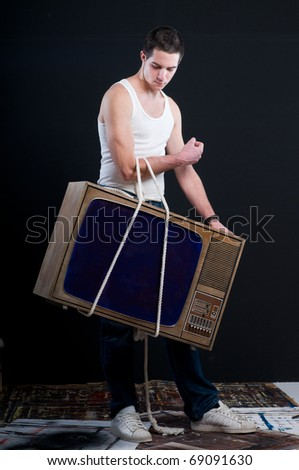 Young man carryng vintage TV on rope to repair its
