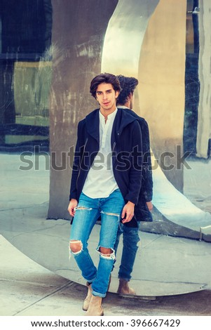 Young Man Casual Street Fashion. American college student, wearing fashionable long coat, jeans, boots, standing against metal mirror wall in New York, looking at you. Instagram filtered effect.  - stock photo