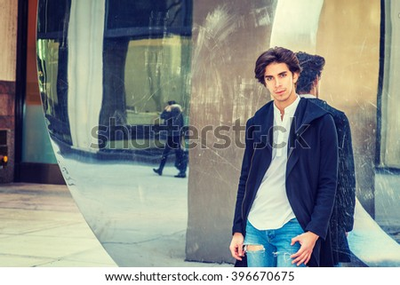Young Man Casual Street Fashion. American college student, wearing fashionable long coat, jeans, standing against metal mirror wall in New York, looking at you, thinking. Instagram filtered effect.  - stock photo