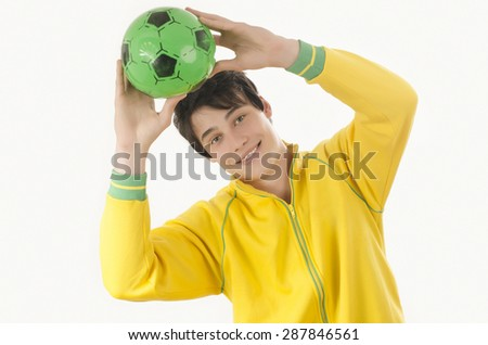 Young man catching a football ball. Attractive man holding a ball in the hands over his head. Isolated on white. - stock photo