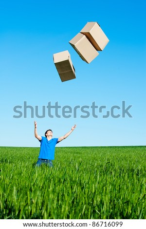 young man catching boxes on green field against blue sky - stock photo