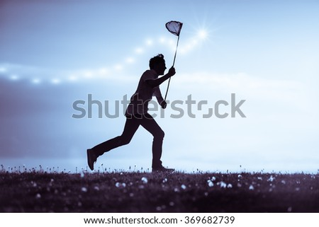 Young man catching insects at dusk running along the skyline silhouetted against a cloudy blue sky brandishing his net - stock photo