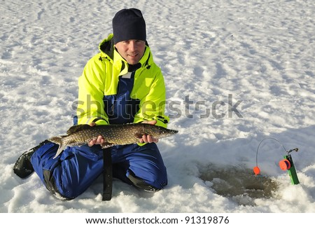 Young man caught a pike from the ice.