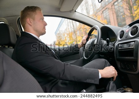 Young Man Changing Gear While Driving A Car - stock photo