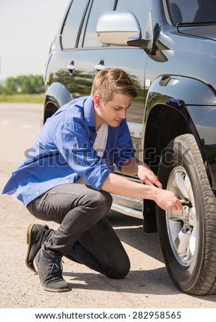 Young man changing the punctured tyre on his car. - stock photo