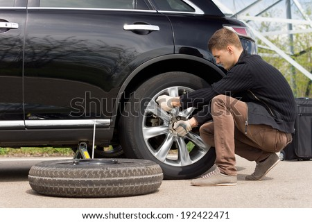 Young man changing the punctured tyre on his car loosening the nuts with a wheel spanner before jacking up the vehicle - stock photo