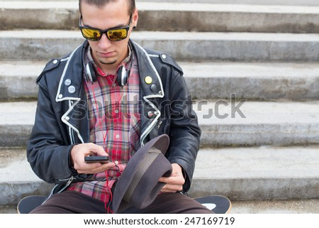 Young man chatting online on his phone. - stock photo
