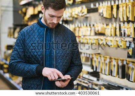 Young man checking a text message on his mobile phone as he shops in a hardware store store for DIY supplies - stock photo