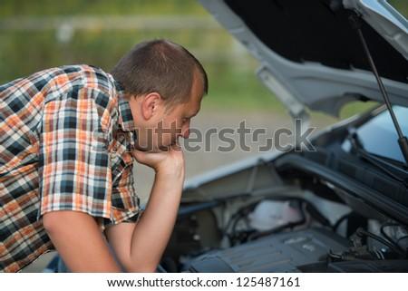 young man checking broken car - stock photo