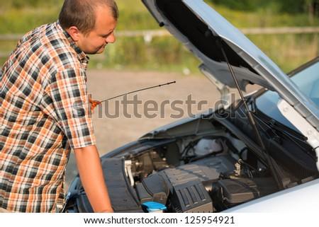 young man checking oil in broken car - stock photo