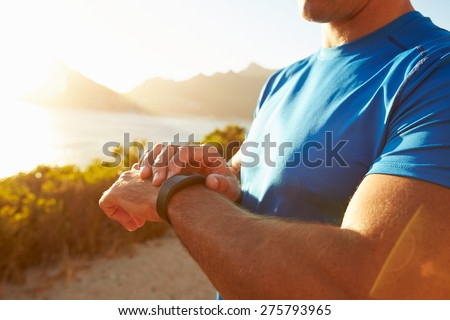 Young man checking time on his sports watch - stock photo