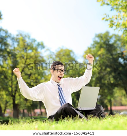 Young man cheering and watching TV on a laptop in a park on a sunny day, shot with a tilt and shift lens - stock photo