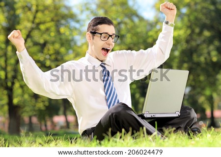 Young man cheering and watching TV on a laptop in park on a sunny day - stock photo