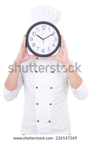 young man chef in uniform holding office clock behind his face isolated on white background