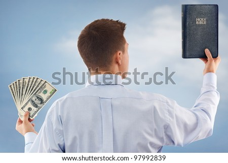 Young man choosing between God and money - stock photo