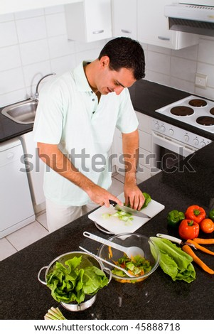 young man chopping vegetables in kitchen - stock photo