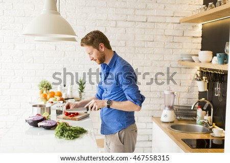Young man chopping vegetables in the kitchen