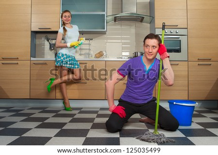 Young man cleaning floor with his girlfriend at kitchen