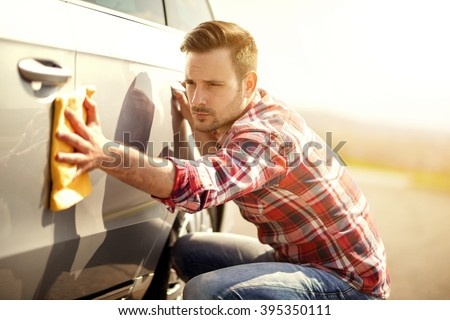 Young man cleaning his car outdoors.Man with a microfiber wipe the car polishing - stock photo