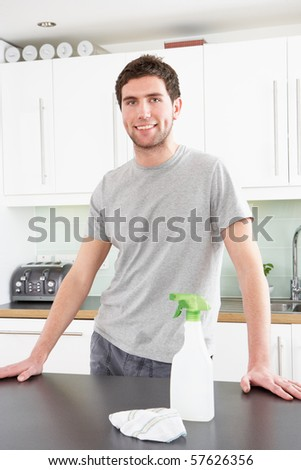 Young Man Cleaning Modern Kitchen - stock photo
