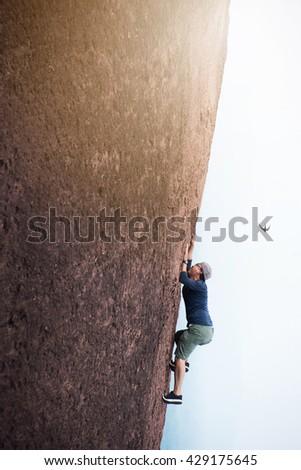 Young man climbing  - stock photo