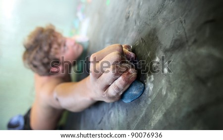 Young man climbing indoor wall. Focus on a fingers - stock photo