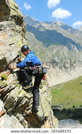 Young man climbing natural rocky - stock photo