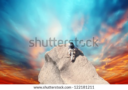 Young man climbing on a limestone wall with blue sky on the background - stock photo
