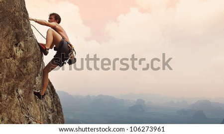Young man climbing on a limestone wall with wide valley on the background