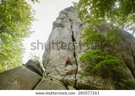Young man climbing on a stone - stock photo