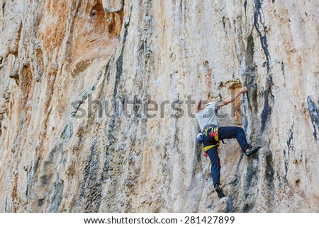 Young man climbing on a wall with quick-draws - stock photo