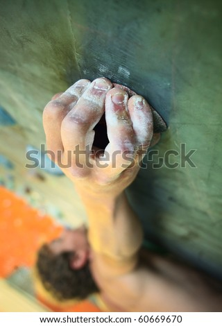 Young man climbing on indoor wall - stock photo