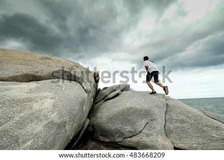 Young man climbing rock in cloudy day