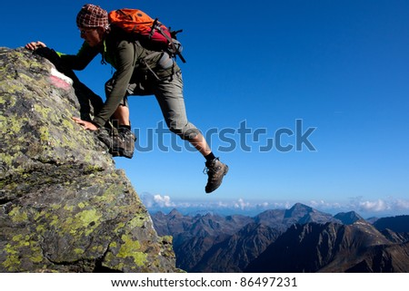 Young man climbing the mountain ridge - stock photo
