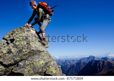 Young man climbing the mountain ridge - stock photo