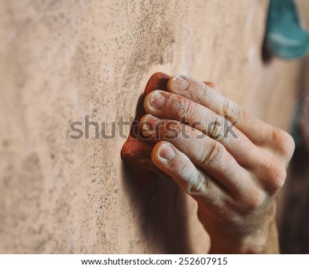 Young man climbing up on wall in gym, close up on hand - stock photo