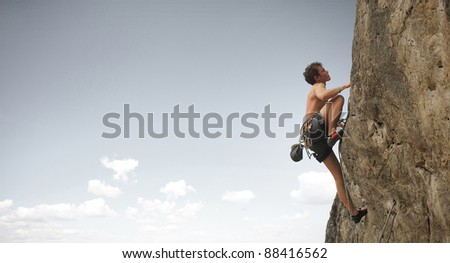 Young man climbs on a cliff on grey sky background