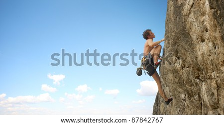 Young man climbs on a cliff over blue sky background