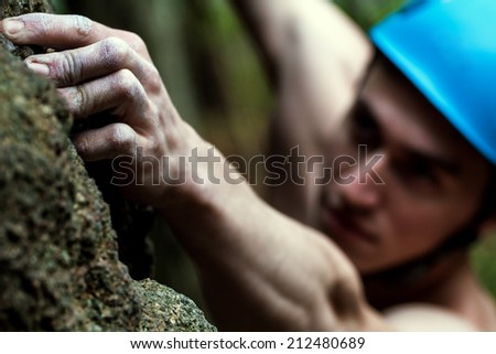 young man climbs on a rock - stock photo