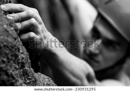 Young man climbs on a rock  Blurred image - stock photo