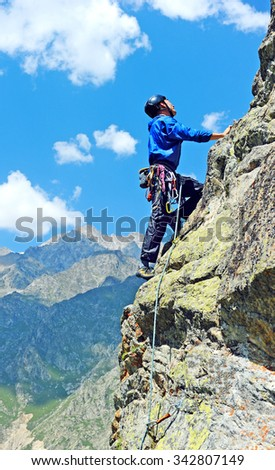 Young man climbs on a rocky wall - stock photo