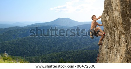 Young man climbs on a rocky wall in a valley with mountains
