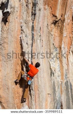 Young man climbs on a rocky wall in a valley with mountains at sunrise. - stock photo