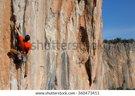 Young man climbs on a rocky wall in a valley with mountains at sunrise.