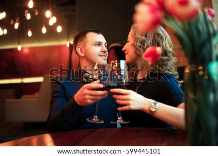 Young man clinks glasses with woman and makes her marriage proposal. They are sitting at the table.