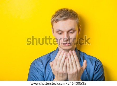 Young man close-up in a blue shirt on a yellow background, reading something or looking at his hands, palms. Mimicry. Gesture. photo Shoot - stock photo