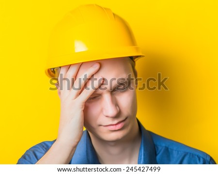 Young man close-up in yellow construction helmet and a blue shirt on a yellow background headache, holding his head by hand. Mimicry. Gesture. photo Shoot - stock photo