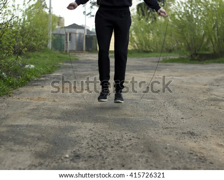 Young man close up on a street in sportswear is jumping on a skipping rope in cloudy weather - stock photo