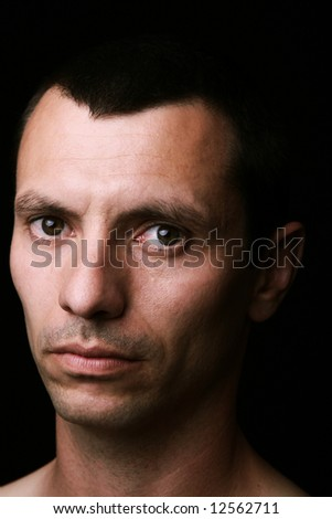 young man close up portrait, on black background - stock photo